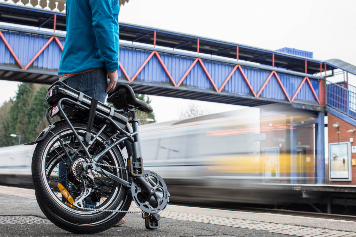 Man with a foldable bicycle at a train station